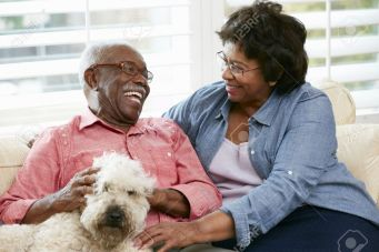 18735709-Happy-Senior-Couple-Sitting-On-Sofa-With-Dog-Stock-Photo