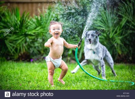 toddler-girl-holding-water-hose-playing-with-dog-E711A1